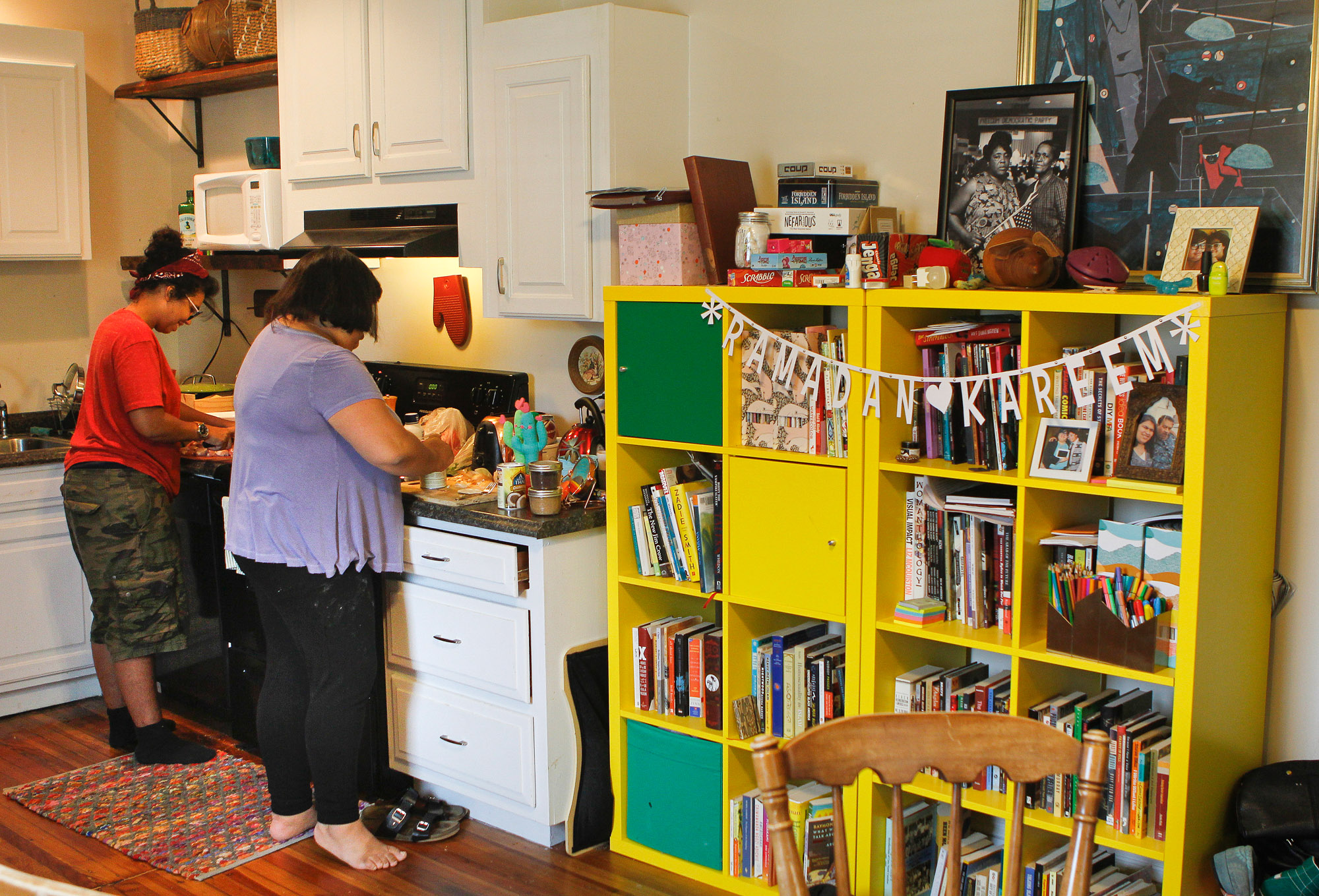 "Two people cook at a stove next to a large yellow bookshelf, where the letters ""Ramadan Kareem"" are displayed on a banner."
