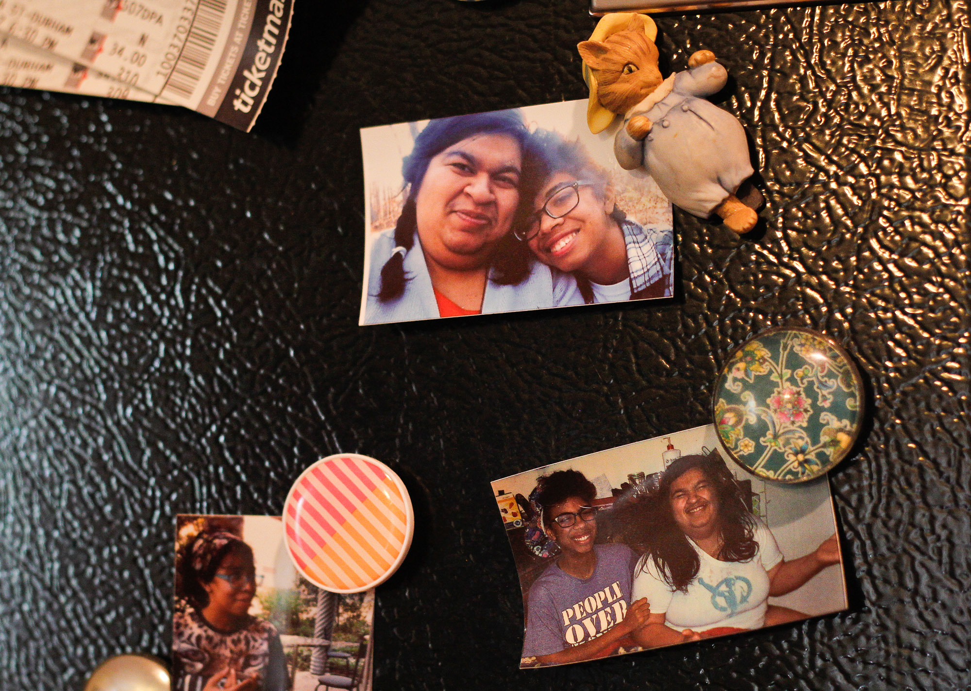 Photographs of Panjwani and Wideman decorate the surface of a black refrigerator.